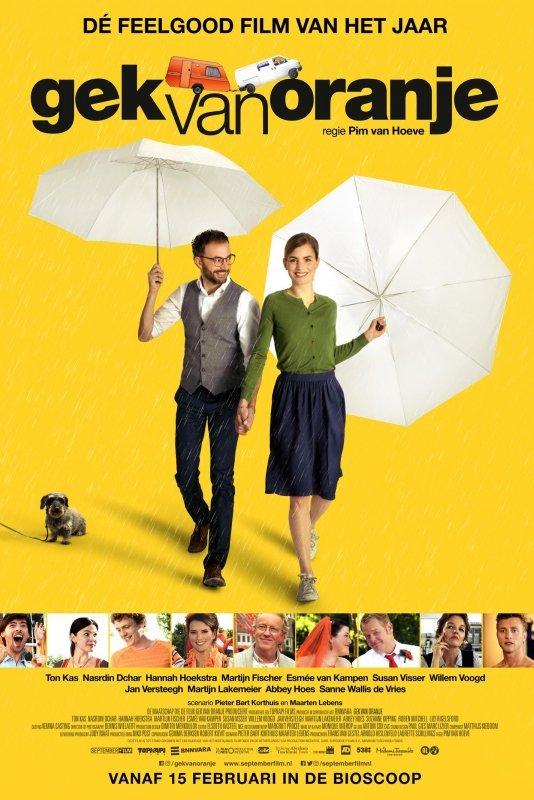 Gek van oranje. Voor een gele achtergrond lopen een jongeman en dame met allebei een witte paraplu hand in hand richting de camera. Daarnaast zit een aangelijnd hondje.