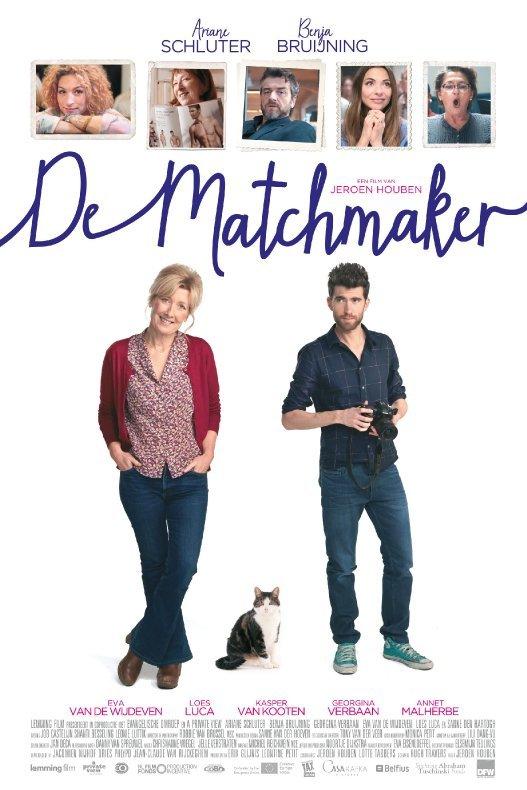 De Matchmaker. Tegen een witte achtergrond staat een vrouw nonchalant naast een mannelijke fotograaf. Daar tussenin zit een kat op de grond.