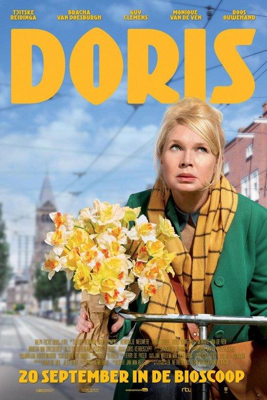 Doris. Een blonde vrouw met groene jas en gele das staat met haar fiets en een bosje narcissen in een Amsterdamse straat en kijkt bedenkelijk omhoog.