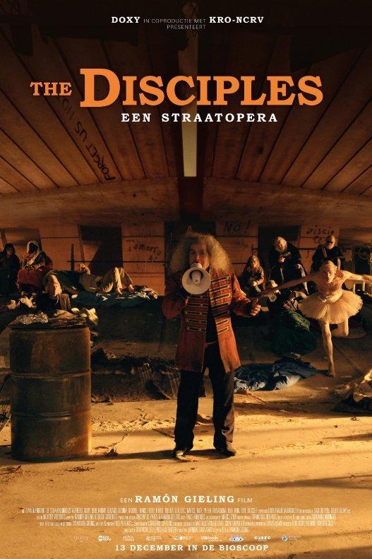 The Disciples - Een straatopera. Een man met een megafoon staat onder een viaduct. Achter hem zitten een aantal daklozen. Een van hen draagt een tutu.