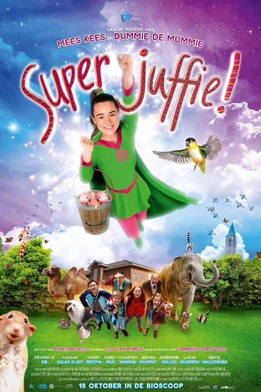 Superjuffie. Een jonge vrouw, in een groen pak met cape, vliegt door de lucht en draagt een emmer met twee biggetjes er in. Op de grond kijkt een groepje mensen en dieren haar na.