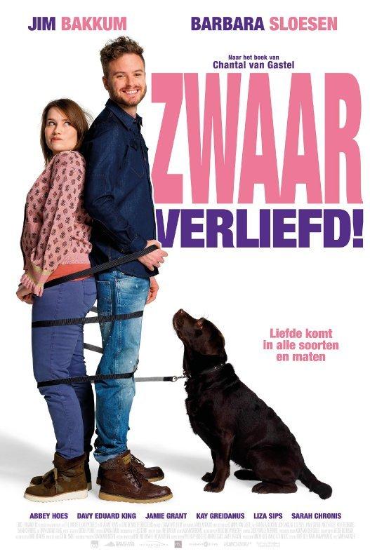 Zwaar verliefd. Liefde komt in alle soorten en maten. Een man en vrouw staan rug aan rug. Een zwarte hond, wiens riem om het stel heen gewikkeld is, zit naast hen en kijkt hen aan.