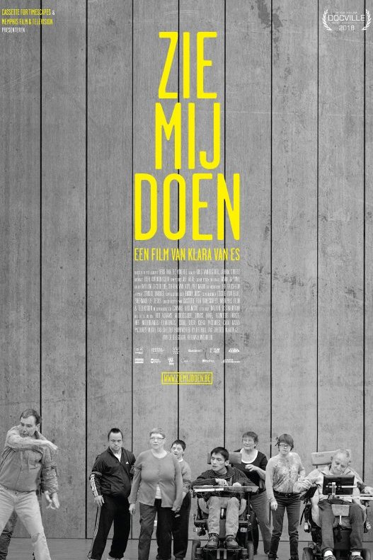 Zie mij doen. Gele letters op een grijze achtergrond. Onder de letters staat een groep mensen, waarvan twee in een rolstoel.