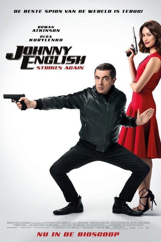 Johnny English Strikes Again. Een man, in zwart gekleed, staat in gevechtshouding met een pistool in zijn hand. Achter hem leunt een vrouw in rode jurk tegen de muur met een pistool in haar hand.