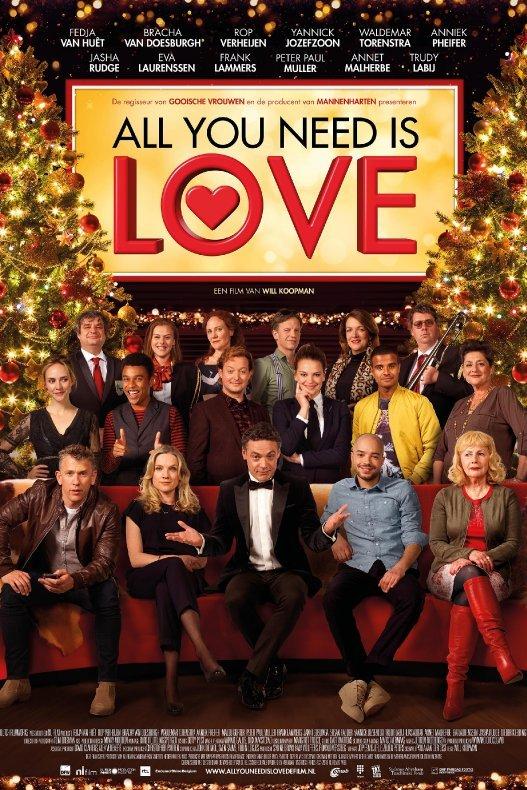 All You Need Is Love. Een groep van 17 personen zit op en om een rode bank tussen twee kerstbomen.
