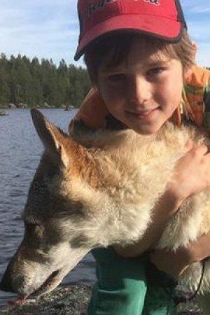 Een jongen omhelst een hond die in een meer staat te drinken.