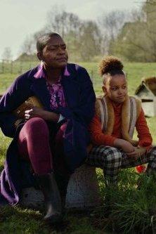 Hiernamaals. Een meisje en een vrouw zitten op een omgekeerde teil in een weiland.