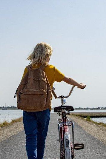 Het irritante eiland. Een kind loopt met een fiets over een dijk.