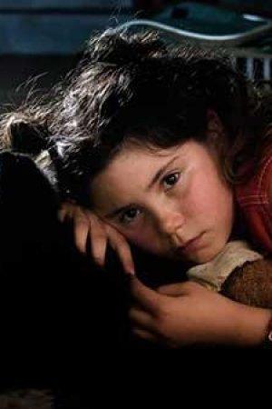 Een meisje ligt met haar hand onder haar hoofd en kijkt dromerig voor zich uit.