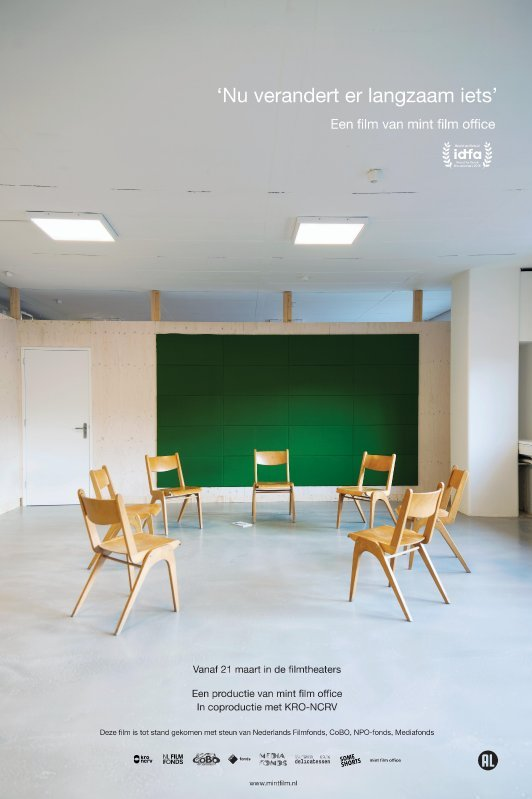 Nu verandert er langzaam iets. Zeven lege stoelen staan in een kring in een verder lege ruimte.