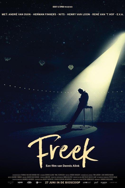 Freek. Freek de Jonge staat in een spotlight op een podium in een donkere zaal, leunend tegen een hoge kruk.