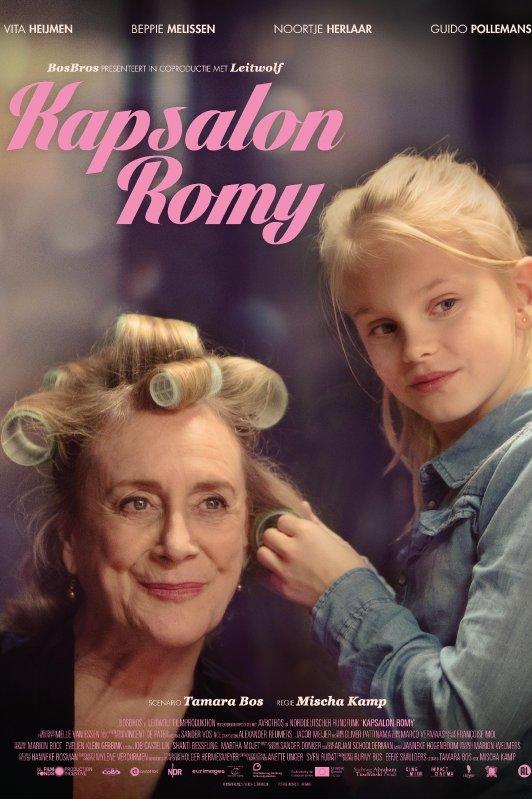 Kapsalon Romy. Een meisje zet krulspelden in het haar van een oudere vrouw.