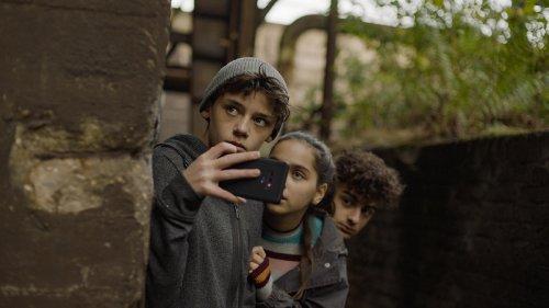 Drie kinderen verstoppen zich achter een muurtje, het voorste kind lijkt met zijn telefoon te filmen.