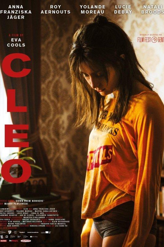 Cleo. Een meisje staat in een kamer en kijkt naar beneden.