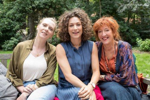 Drie vrouwen zitten naast elkaar en kijken lachend voor zich uit.