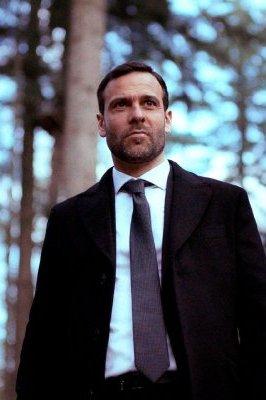 Hallali. Een man met pak staat in het bos.