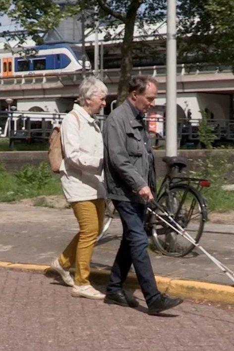 Op de tast. En blinde man en vrouw lopen gearmd en met witte stok over straat.