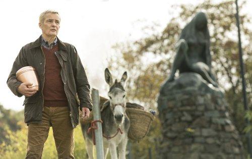 Een man met een urn in zijn hand staat buiten, naast een ezel.