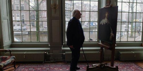 Een grijze man met een stok kijkt naar een schilderij van Rembrandt.