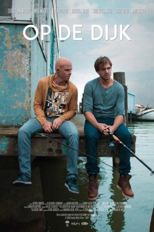 Op de Dijk. Twee jongens zitten op een steiger te vissen. Een van de twee jongens is kaal en zit vol littekens van brandwonden.