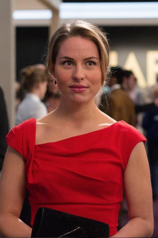 Fake: een vrouw met blond opgestoken haar draagt een rode jurk en heeft een zwarte clutch vast.
