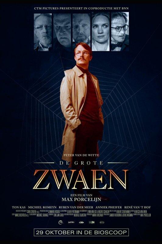 Een man in beige trenchcoat staat met zijn handen in zijn zakken en kijkt zijdelings weg. Achter hem een spinnenweb.