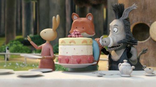 Vos, Haas en een everzwijn staan aan een tafel waarop een hele grote taart  staat.