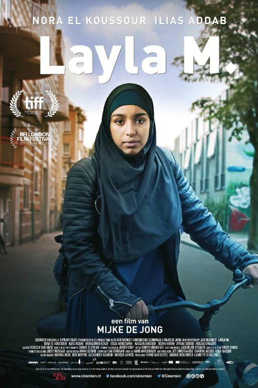Layla M. Een jonge vrouw met zwarte hoofddoek en leren jas zit op een fiets en kijkt onbewogen voor zich uit.