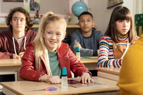 Een meisje zit lachend in de klas.