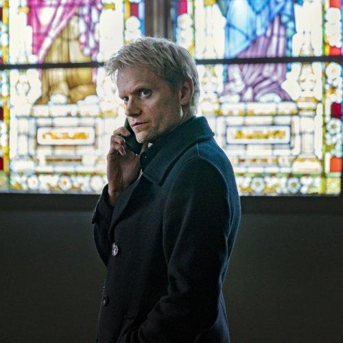 Detective van der Valk houdt zijn telefoon naast zijn hoofd. Hij is aan het bellen. Achter hem is een groot glas in lood raam.
