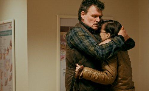 Een vrouw in een bruin leren jack omhelst emotioneel een man met donker, krullend haar.