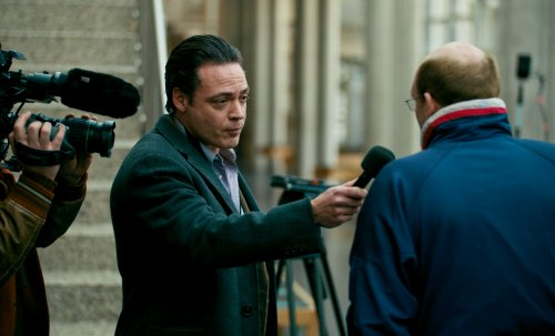 Een journalist staat buiten en vraagt iets aan een kalende man.