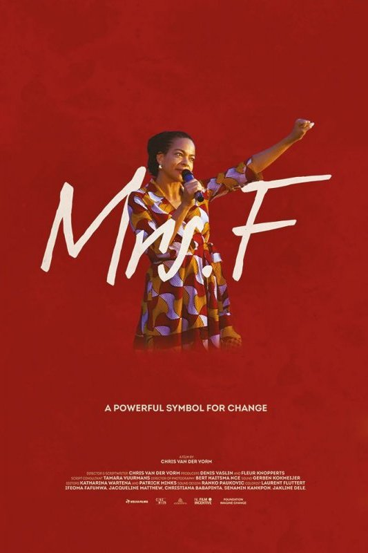 Mrs. F. A powerful symbol for change. Een vrouw met donker haar heeft haar ene arm in de lucht en met haar andere arm houdt ze een microfoon vast.