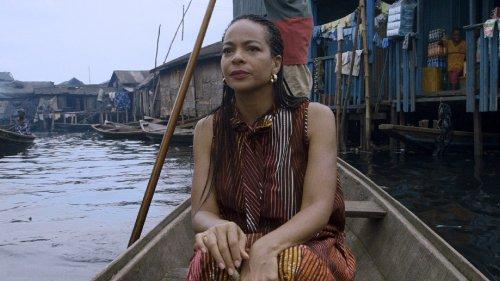 Een vrouw met donker haar in kleine vlechtjes vaart in een bootje door een sloppenwijk.