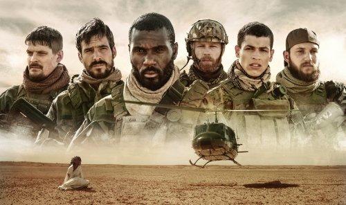 Een groep mannen in militaire kleding met daarvoor een helikopter die gaat landen.