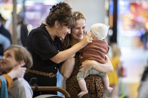 Iris kijkt blij naar haar kind in haar armen. Een oudere vrouw staat naast haar en raakt het kind liefdevol aan.