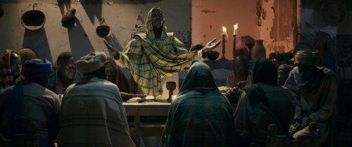 Het laatste avondmaal: Een man staat met zijn handen geheven en zijn ogen dicht aan het lange eind van een tafel waar meer donkere mannen aan zitten.