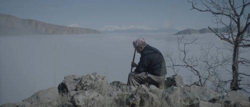 Een man met een tulband op zijn hoofd en een stok in zijn hand zit met gebogen rug op rotsen aan de rand van een meer.