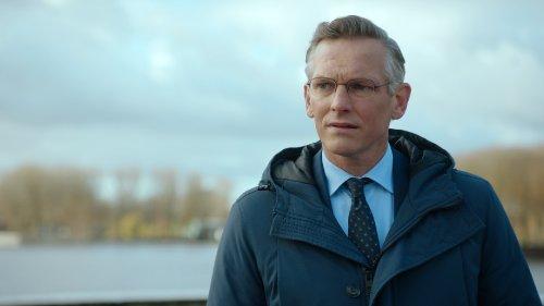 Een nette, grijze man met een bril op kijkt bedenkelijk.