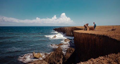 Een man en een vrouw staan bij een kist aan de rand van een klif aan zee.
