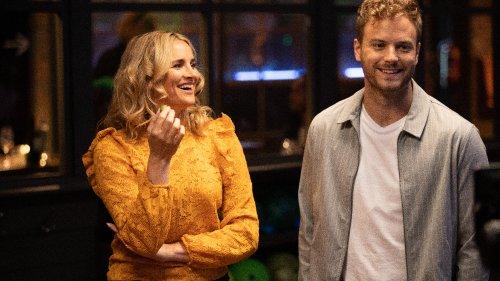 Een mooie vrouw met blonde krullen kijkt lachend naar een knappe, blonde man die lachend een andere kant op kijkt.