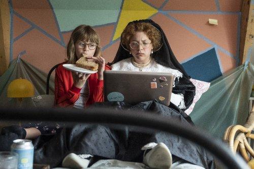 De blonde vrouw Oopjen zit in haar zeventiende-eeuwse kledij naar een laptop te turen. De 12-jarige Jackie zit naast haar en kijkt mee.