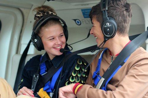 Een meisje en een jongen zitten in een helikopter met grote koptelefoons op. Ze lachen lief naar elkaar.