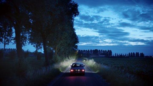 Een auto rijdt over een donker weggetje langs een akker.