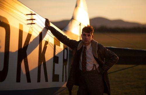 Een jonge Anthony Fokker staat tegen een oud vliegtuig geleund.