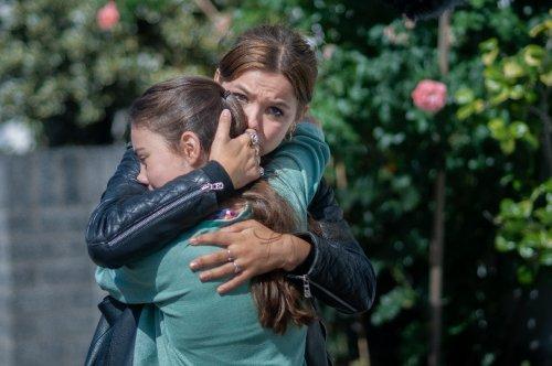 Een vrouw en meisje knuffelen elkaar innig.