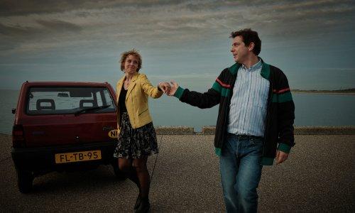 Ischa en Connie lopen hand in hand (alsof ze dansen) over een dijk langs een geparkeerde bordeauxrode Fiat Panda. Ze kijken elkaar verliefd in de ogen.