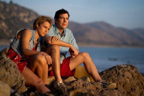 Een blonde vrouw en een donkerharige man zitten dicht bij elkaar in de zon op rotsen aan zee.