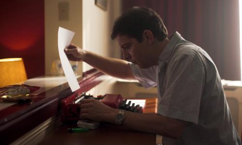 Een man rolt een stuk papier in een rode typemachine. Daarnaast liggen een pakje Lucky Strike sigaretten en een aansteker.