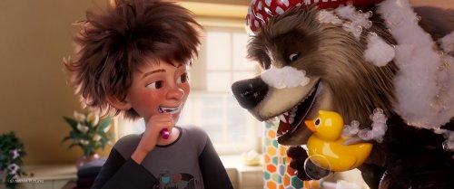 Een jongen met wild, bruin haar poetst zijn tanden en kijkt blij naar een lachende beer met een badmuts op en een badeend in z'n hand.